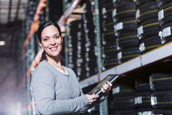 Female staff member next to shelves of car tyres