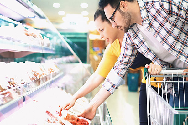 Couple choosing meat in the supermarket