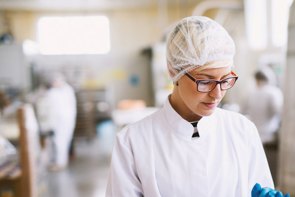 Lady preparing food in factory